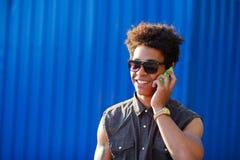 Szczęśliwy młody czarnego afrykanina mężczyzna z telefonem komórkowym ma rozmowę na wiszącej ozdobie Zdjęcie Stock
