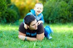 Szczęśliwy ojciec i syn bawić się na zieleni polu Obrazy Royalty Free