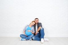 Szczęśliwy para mąż i ciężarna żona blisko pustego ściana z cegieł Zdjęcia Royalty Free