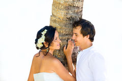 Szczęśliwy państwo młodzi ma zabawę na tropikalnej plaży pod p Zdjęcia Stock