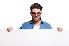Szczęśliwy przypadkowy mężczyzna trzyma białą deskę Zdjęcie Royalty Free