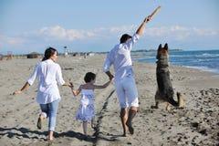 Szczęśliwy rodzinny bawić się z psem na plaży Zdjęcia Royalty Free