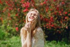 Szczęśliwy uroczy blond żeński obsiadanie w kwitnienie ogródzie, kobieta z zamkniętymi oczami cieszy się piękno natura, relaks pr Obrazy Royalty Free