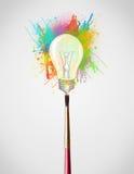 Szczotkarski zakończenie z barwionymi farb pluśnięciami, lightbulb i Fotografia Stock