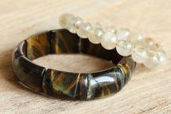 Szczęsliwe kamienne bransoletki na drewnianym tle Fotografia Stock