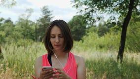 Szczupła atrakcyjna dziewczyna w menchia wierzchołku stawia dalej hełmofony Sportive kobieta zaczyna słuchać muzykę na smartphone zbiory wideo