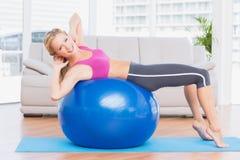 Szczupła blondynka podnosi na ćwiczenia balowy ono uśmiecha się przy kamerą robić siedzi Fotografia Royalty Free