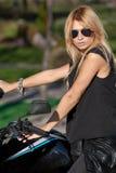 Szczupła blondynka pozuje blisko motocyklu obrazy stock