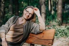 Szczupła blondynka siedzi na drewnianej ławce obrazy stock