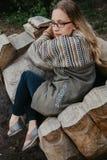 Szczupła blondynka siedzi na drewnianej ławce obraz stock