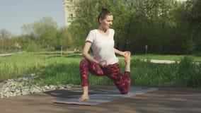 Szczupła brunetka robi joga skrętowi w parku zbiory