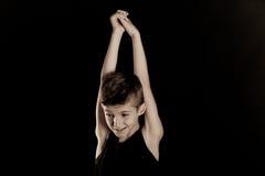 Szczupła chłopiec Podnosi jego ręki Przeciw Czarnemu tłu Fotografia Stock