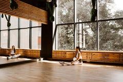 Szczupła ciemnowłosa dziewczyna ubierająca w białych sportach stać na czele lustro blisko okno w gym ubrania siedzą na pod zdjęcie royalty free