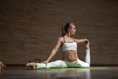 Szczupła dama dotyka ona palec u nogi podczas gdy rozciągający ona nogi na joga matują obraz royalty free