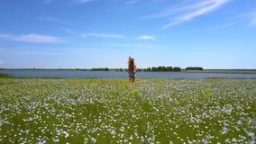 Szczupła dziewczyna biega na gryki polu odległy jezioro zdjęcie wideo