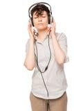 Szczupła dziewczyna cieszy się muzykę z hełmofonami odizolowywającymi obrazy stock
