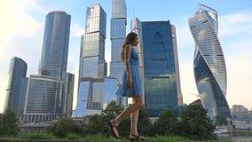 Szczupła dziewczyna w błękit sukni odprowadzeniu przeciw nowożytnym drapaczom chmur, super zwolnionego tempa wideo, 250 fps zbiory wideo