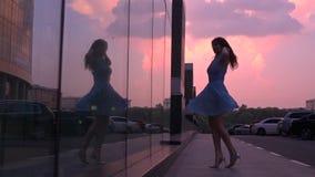 Szczupła dziewczyna w błękit sukni tanu na ulicie przy różowym zmierzchem, super zwolnione tempo strzał, 250 fps zbiory