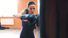 Szczupła dziewczyna w bokserskich rękawiczkach bije uderzać pięścią torbę w Gym z ogłoszenie towarzyskie trenerem Trening z instr zbiory