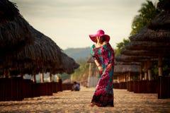 szczupła dziewczyna w czerwonych kapeluszy spojrzeniach w niebo wśród defocused parasoli Obraz Stock