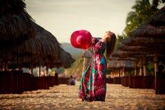 szczupła dziewczyna w czerwonych kapeluszy spojrzeniach w niebo wśród defocused parasoli Zdjęcia Stock