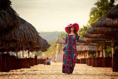 szczupła dziewczyna w długich i dużych czerwonych kapeluszy stojakach wśród plażowych parasoli Fotografia Royalty Free