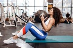 Szczupła kędzierzawa ciemnowłosa dziewczyna ubierał w sportach odziewa robić ćwiczeniom dla prasy na macie dla sprawności fizyczn zdjęcia stock