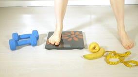Szczupła kobieta chwyta miara na tle talerz z owoc i warzywo, zdrowy styl życia zbiory wideo