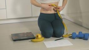 Szczupła kobieta chwyta miara na tle talerz z owoc i warzywo, zdrowy styl życia zbiory