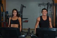 Szczupła kobieta i mięśniowy męski trener w sporta gym Zdjęcia Stock