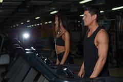 Szczupła kobieta i mięśniowy męski trener w sporta gym Obraz Royalty Free