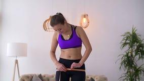 Szczupła kobieta mierzy jej biodra z pomiarową taśmą zbiory wideo