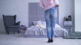 Szczupła kobieta w dużych spodniach po gubienia obciąża w domu zbiory