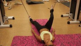 Szczupła młoda dziewczyna pracuje mocno w gym na podłoga zbiory wideo