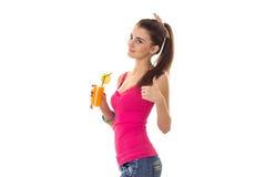 Szczupła młoda dziewczyna w jaskrawej koszulce stoi z ukosa i mienie w jego ręce sok Obraz Stock