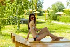 Szczupła młoda dziewczyna w kostiumu kąpielowym na plażowym Lounger zdjęcia royalty free