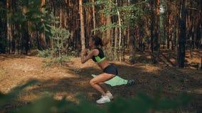 Szczupła młoda dziewczyna w zmroku wierzchołku i skrótach robi ćwiczeniu na stopie zdjęcie wideo