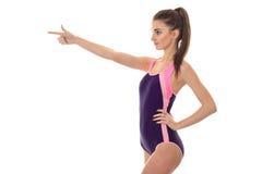 Szczupła młoda kobieta patrzeje oddalony w ciała swimsuit i punktach z palcem na boku odizolowywającym na białym tle obrazy royalty free