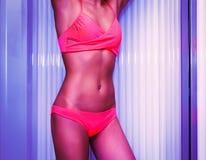Szczupła młodej kobiety pozycja w solarium dostaje suntan Obrazy Royalty Free