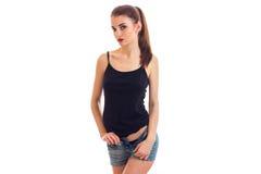 Szczupła piękna dziewczyna z ogonu stojakami przed kamerą w skrótach i czarnej koszulce Fotografia Stock