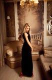 Szczupła plciowa blondynki kobieta w długich czerni smokingowych i czerwonych szpilkach fotografia stock