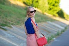 Szczupła wysoka blondynki dziewczyna w błękita wierzchołku i świetle - różowa spódnica jest ubranym okulary przeciwsłonecznych z  obraz royalty free
