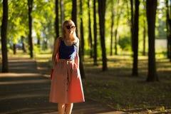 Szczupła wysoka dziewczyna jest ubranym okulary przeciwsłonecznych w błękitnym wierzchołku z blondynem i zaświeca spódnicowych sp obrazy stock