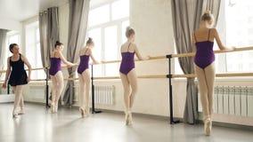 Szczupłe dziewczyny w leotards i baletniczych kapciach robią plie i odprowadzeniu na tiptoe mienia baletniczym barre podczas zbiory