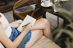 Szczupły dziewczyny obsiadanie na beżowej rzemiennej kanapie i rysunku Obraz Stock