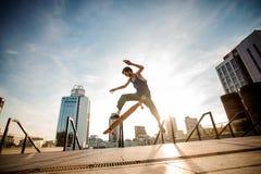 Szczupły młodego człowieka doskakiwanie na deskorolka przeciw miasto budynkom zdjęcie royalty free