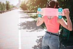 Szczupła i budująca melomaniac dziewczyna pozuje Jest trwanie kamery i mienia łyżwa na szyi z powrotem Ona mieć obraz stock