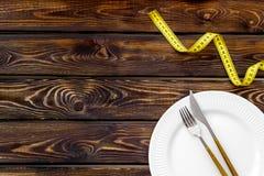 Szczup?y poj?cie z talerzem, flatware i pomiarow? ta?m? na drewnianym t?o odg?rnego widoku mockup, zdjęcia stock