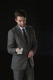 Szczwany biznesmen daje dolarowym banknotom odizolowywającym na czerni Zdjęcia Stock