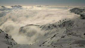 Szczyt góry w ośrodku narciarskim wtyka out od niskiej mgły. zdjęcie wideo